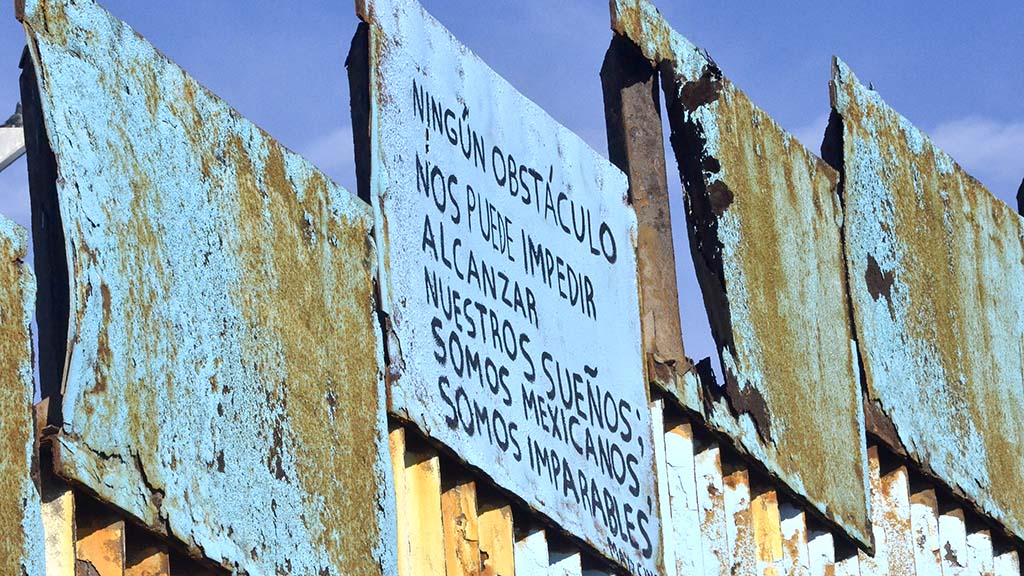 "A sign saying in Spanish, ""No obstacle can prevent u from reaching our dreams. We are Mexicans, we are unstoppable"" was painted on the Mexican side of the border fence."