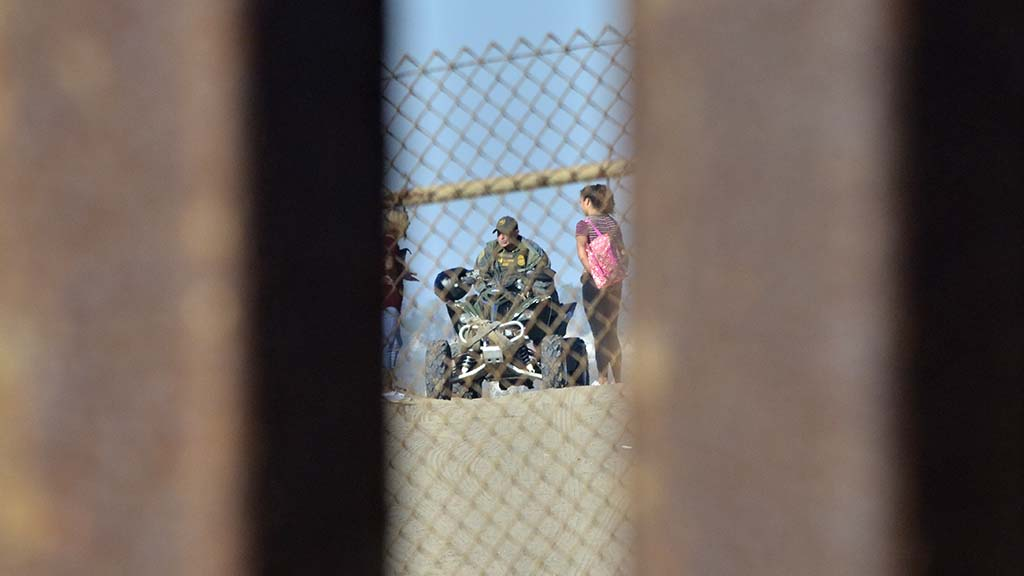 A Border Patrol agent on a all terrain vehicle talks to two women on the U.S. side.