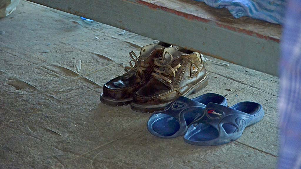 Shoes of migrants sit on the floor of a shelter near the border.