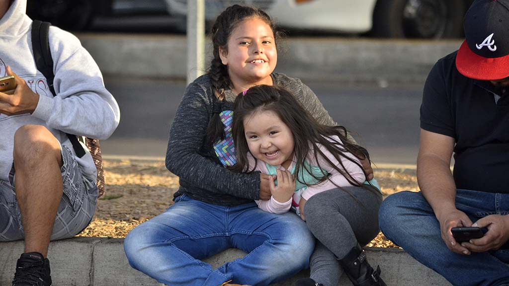 Two girls share a sister moment as the wait with their family members outside the San Ysidro Port of Entry.