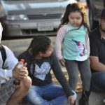 A family waits outside the San Ysidro Port of Entry where thousands of names are on a waiting list.