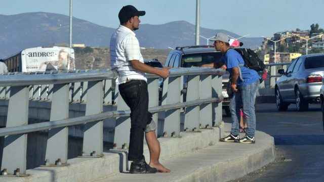 A man in need of medical attention stands on a bridge with other caravan members as they watch the border crossing.