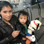 Immigrant mother and child at the downtown bus station