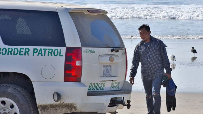 A man from Nicaragua who walked onto the U.S. beach was walked to a Border Patrol SUV to be processed for illegal entry.