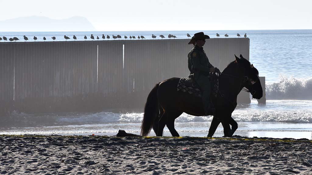 Border Patrol agents on horseback patrol along the fence and beach.
