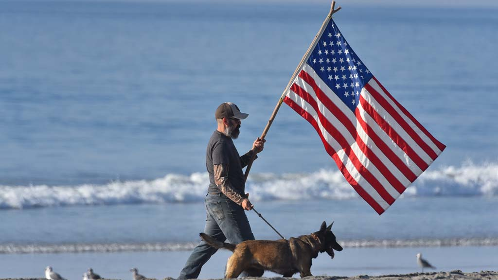 A man carrying a flag on a branch walked around the perimeter of the press conference at the beach.