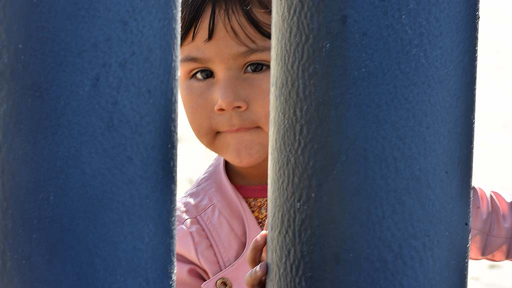 A little Honduran girl peers past the posts into the U.S. territory.