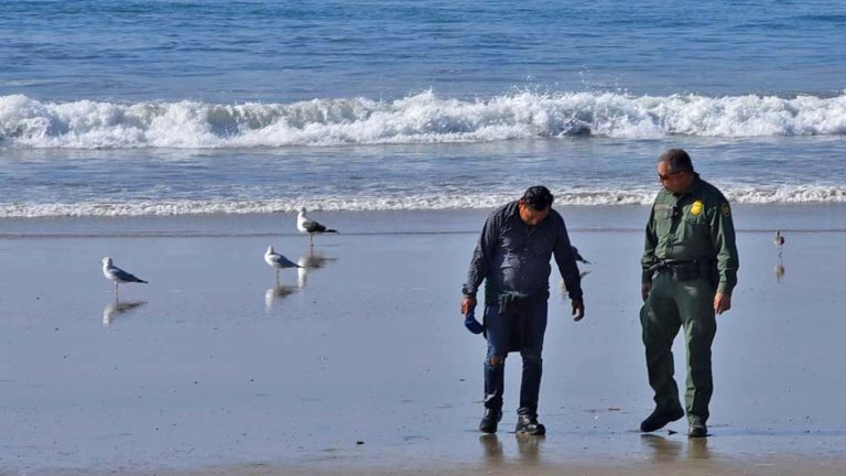 A man with a soaking wet polka dot shirt and tore jeans walked around the border fence an hour before low tide.