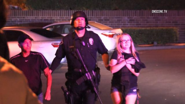 SWAT team officer leads people out of the bar