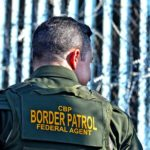 A Border Patrol agent looks at people on the Mexico side of the border fence.