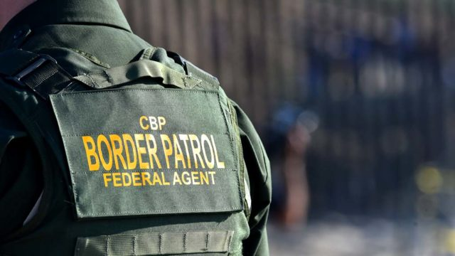 A Border Patrol agent is positioned by the border fence.