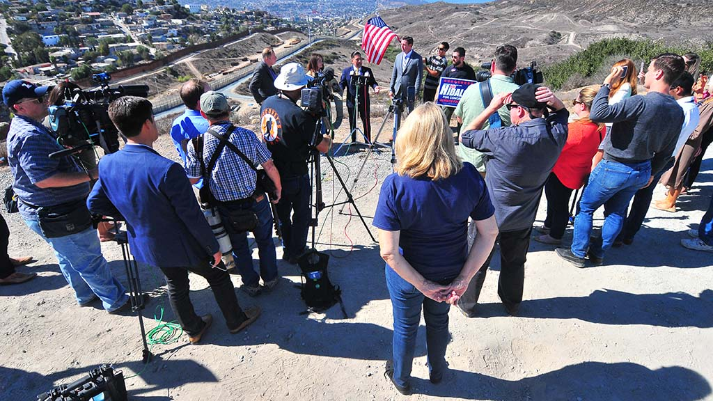 Juan Hidalgo Jr. speaks to media with Mexican border in the background.