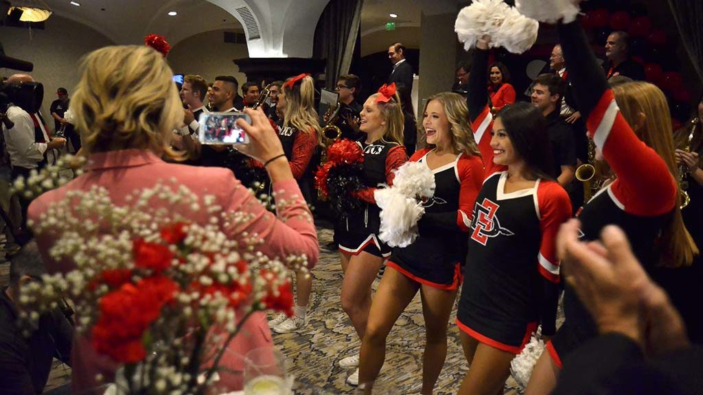 SDSU cheerleaders, backed by the Aztec Pep Band, celebrate voter approval of Measure G.