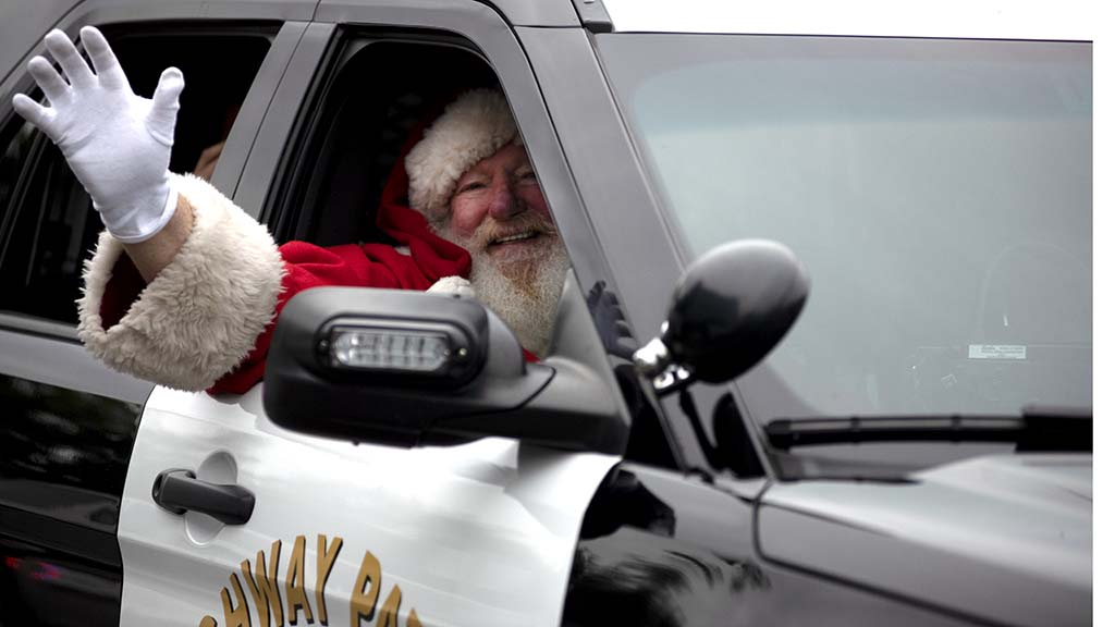 Santa arrives in Barrio Logan via and CHP cruiser for the CHiPs for Kids toy giveaway.