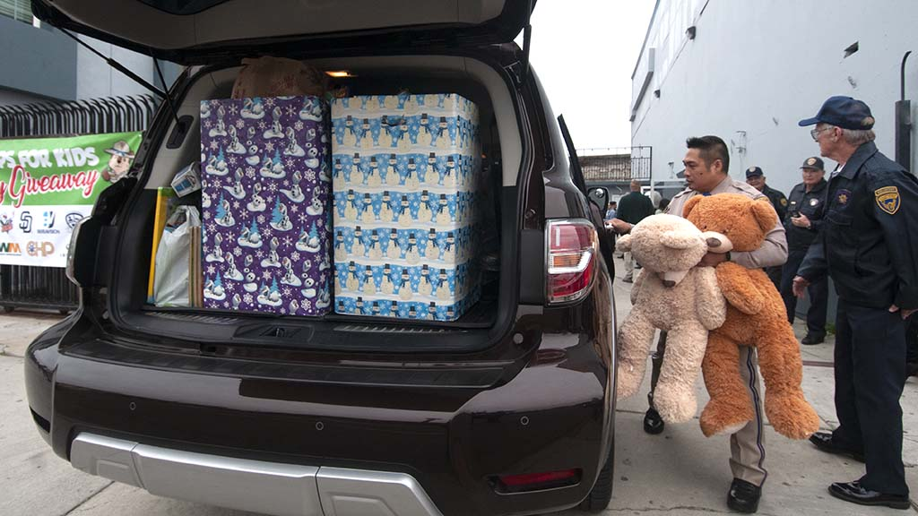 A CHP officer begins to take gifts for children from a van.