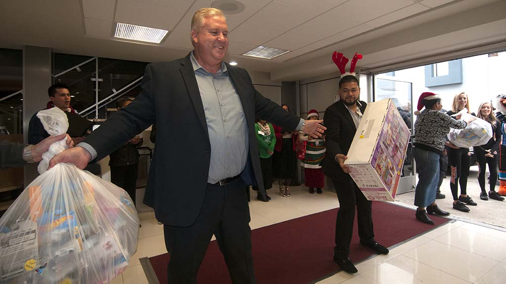 Jack Freeman (center) and Santiago Reyes help bring in the gifts brought by CHP officers.