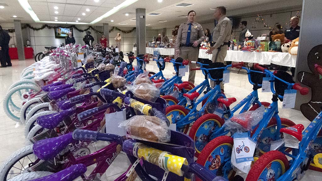 CHP officers stand ready for the children to enter the room filled with toys.