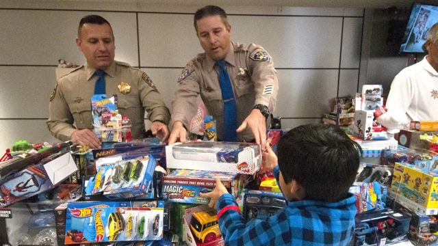 Highway Patrol officers help a young boy choose a toy at the CHiPs for Kids event in Barrio Logan.