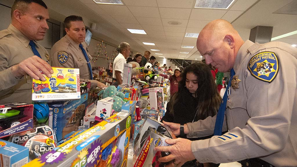 CHP officer Travis Garrow (right) helps a girl find a remote-controlled car.
