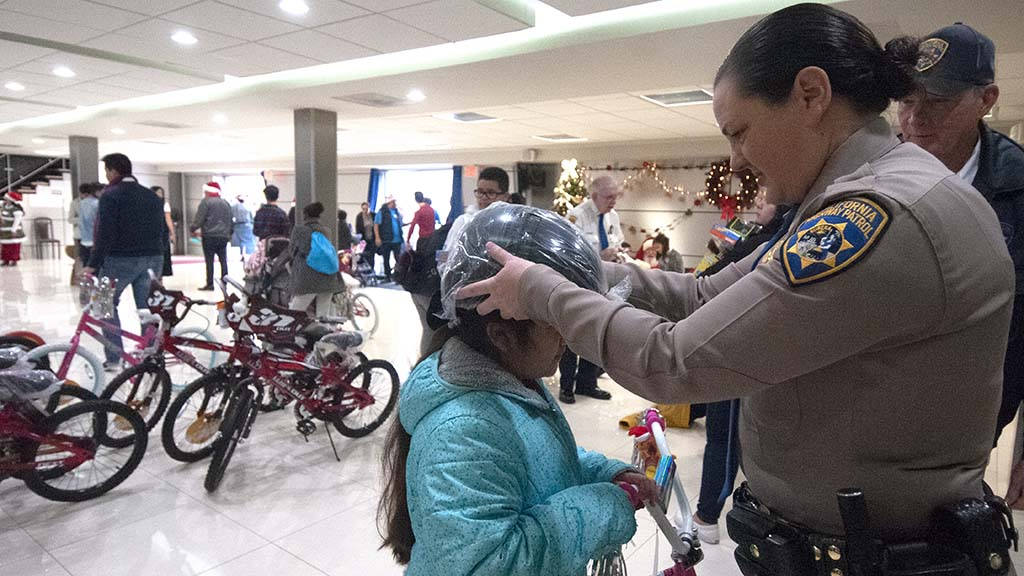 CHP Officer Mary Bailey fits a helmet on Isabella, 8.