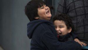 Abdiel Sunem and Levi Reinaga laugh with delight as Santa arrives in Barrio Logan.