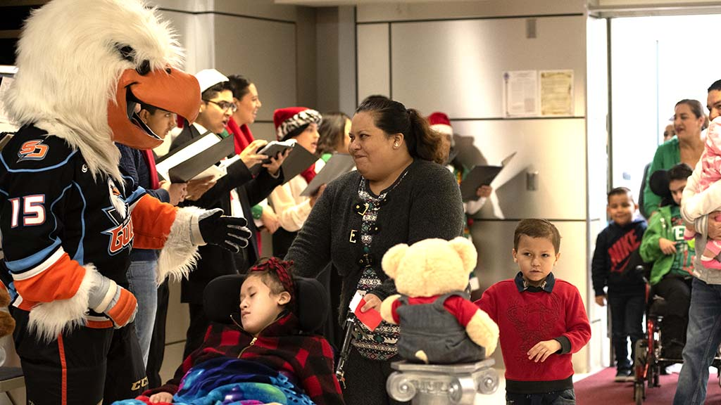 The church choir and mascot for the San Diego Gulls greets parents and children.