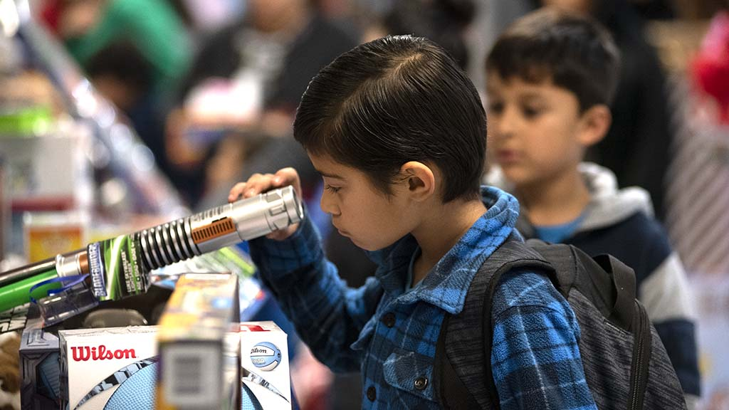 A young boy takes aim at the gift of his choice at the gift giveaway.