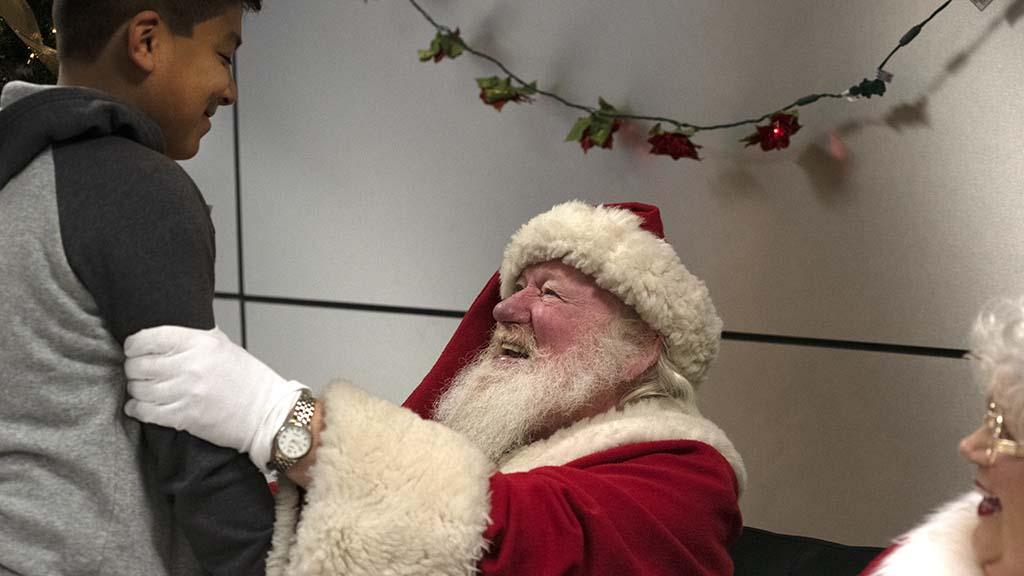 Jehu Perez, 12, has a happy moment with Santa (Bill Swank).