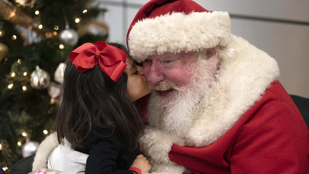 Merari Coronado, 4, gives Santa peck on the cheek.