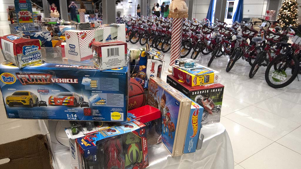 Sixty-two bicycles and stacks of toys awaited the children lined up down Logan Avenue in Barrio Logan.