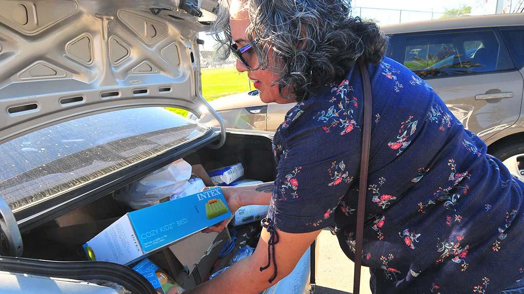High school teacher Cristina Malo loads items into her car before driving to Tijuana.