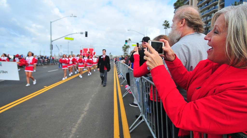 Wearing Utah red, a spectator records the passing Utes cheerleaders.