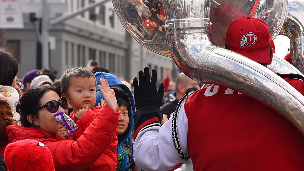 Utah band member gives a gloved high-five to Holiday Bowl Parade spectators.