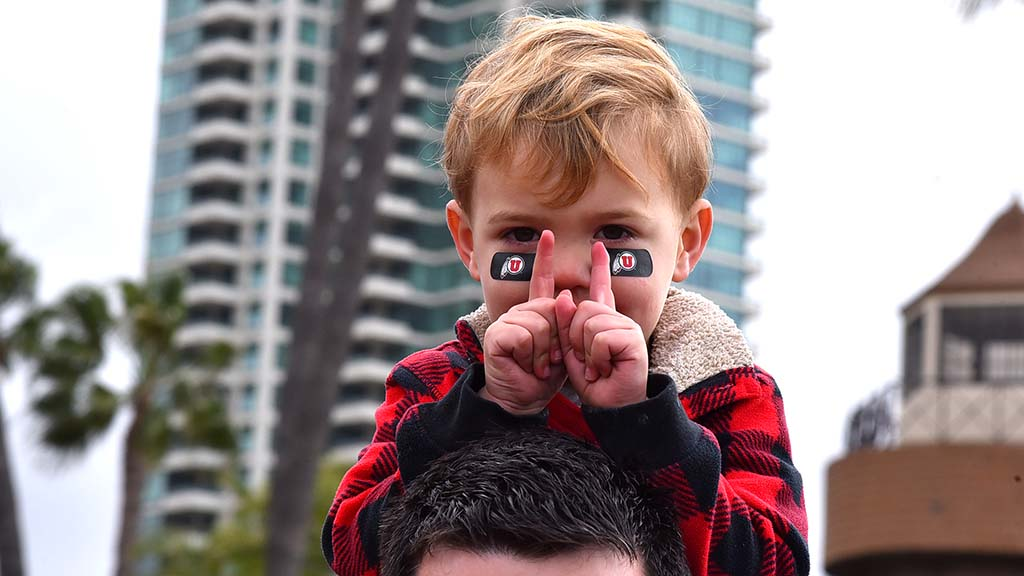 Utah fan Braxton Muehle, 2, does the Utes sign atop shoulders of alumnus father from Las Vegas.