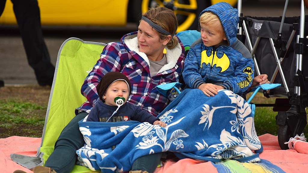 Young family enjoys sights and sounds of the Holiday Bowl Parade.