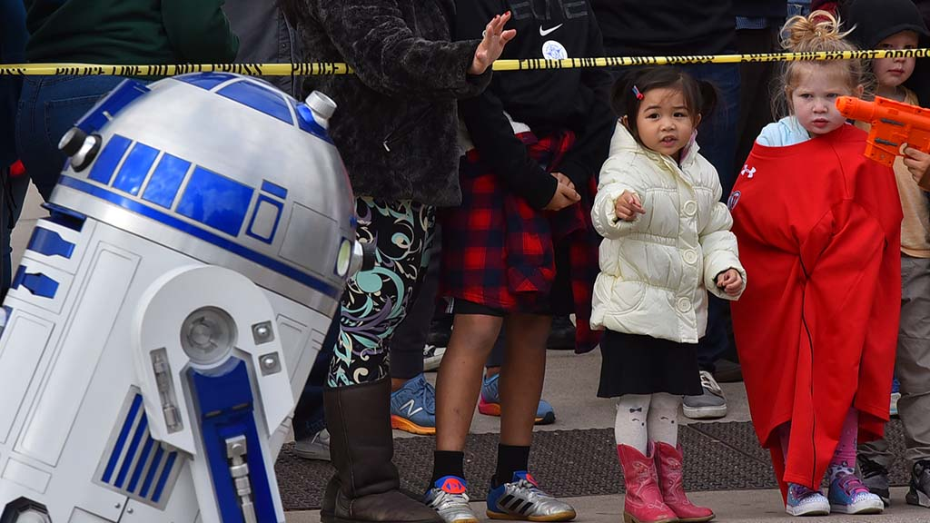 R2-D2 catches the eye of children along Holiday Bowl Parade route.