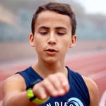 "Joel Gomez, wearing singlet of his former San Diego Waves Track Club, sings ""Running Blind"" in a YouTube video."