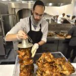 Employee Levy Ceitlin removes cooked kosher chicken from a bell rotisserie at UCSD.
