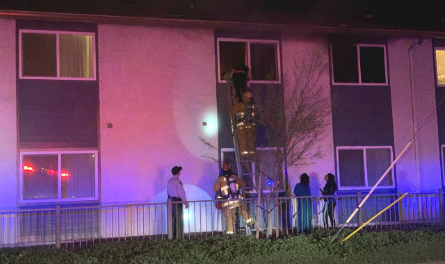 Firefighters rescue a woman from the burning Lakeside apartment