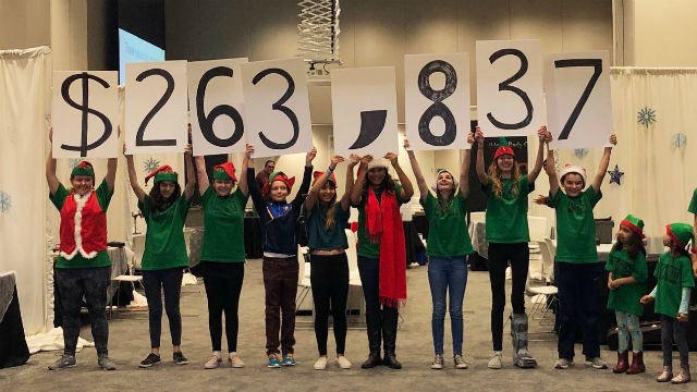 Children hold posters showing the amount raised for Rady Children's Hospital