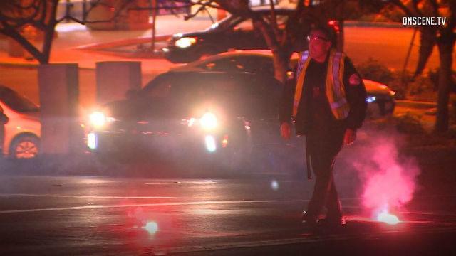 Oceanside Police officer walks by flares