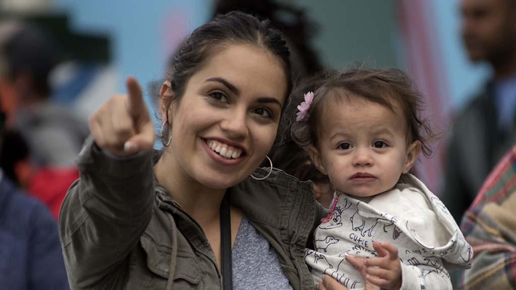 A mother points out parade participants along University Avenue.