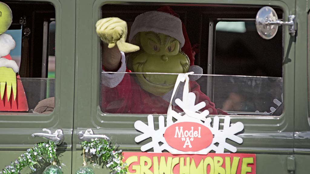 The Grinch gives a thumbs down sign to children who booed him along the route.