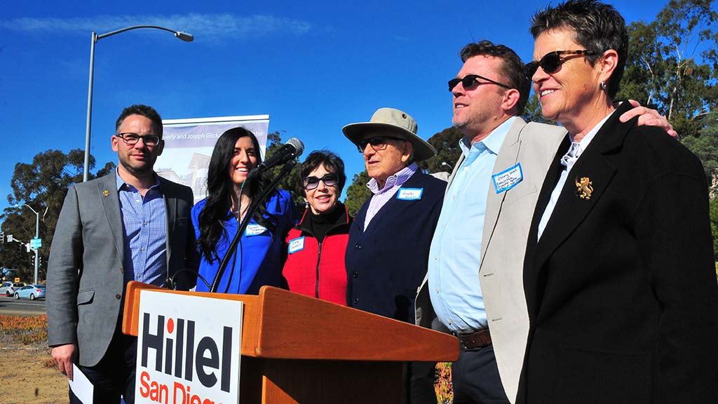 Leaders of the effort to build the Beverly and Joseph Glickman Hillel Center gather in front at the end of the ceremony.