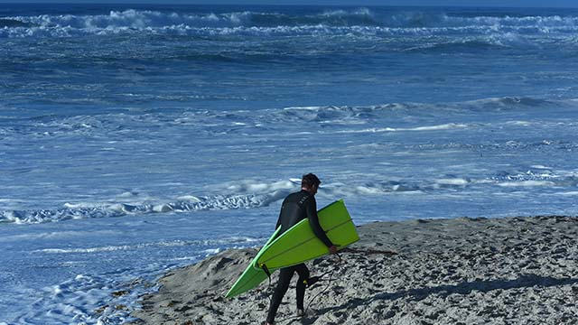 A surfer leaves the beach after his board was broken in half by the high waves.