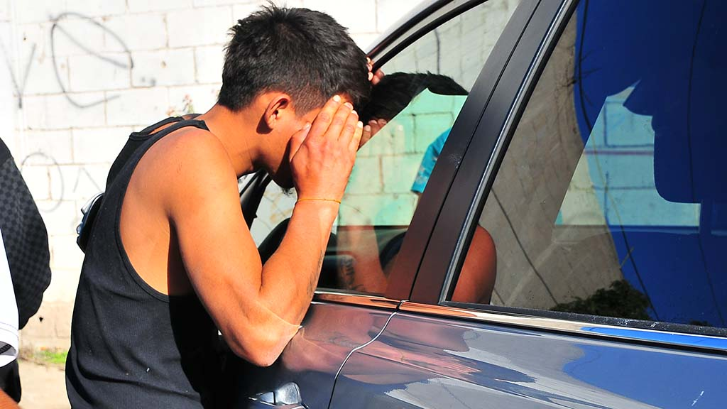 A young migrant peeks into a volunteer's car to see what donations have arrived.