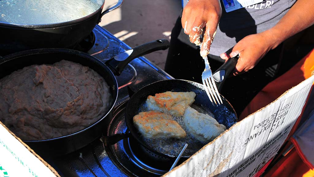 Two women cooked up chicken and beans in the family tent area.