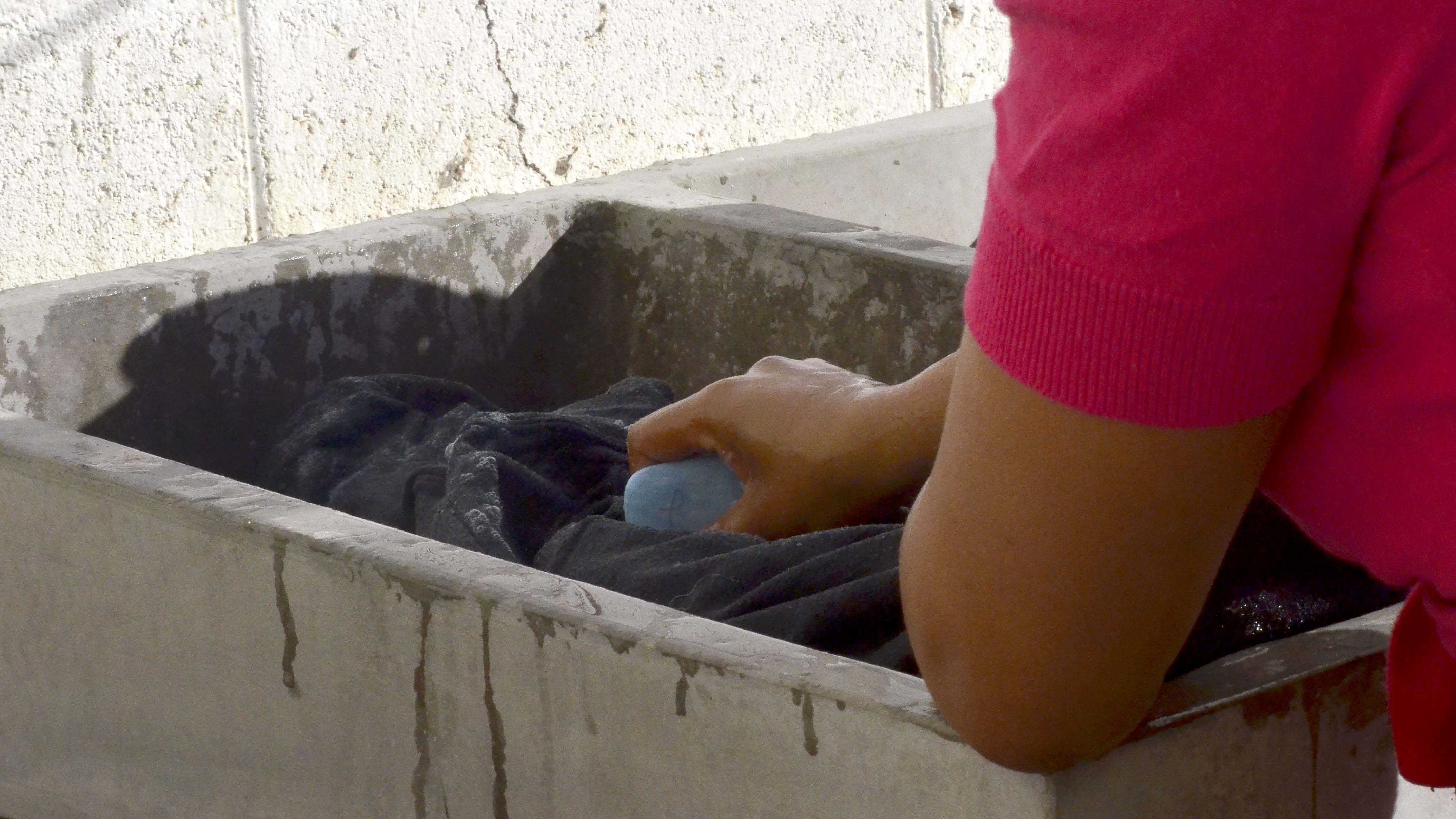 A female migrant uses bar soap to clean her clothes as a line of migrants wait their turn in the courtyard.