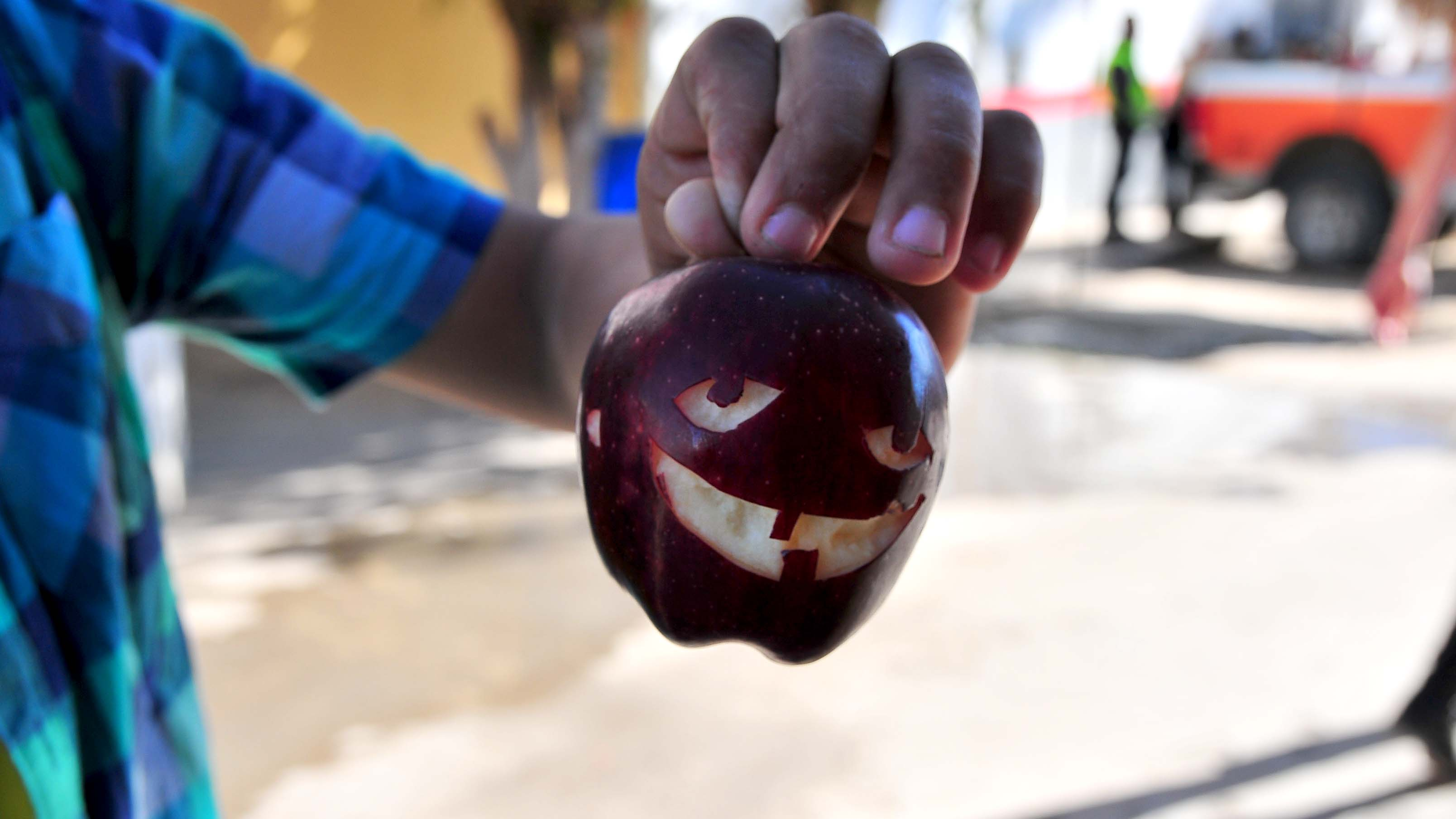 A young migrant shows an apple that he creatively carved.