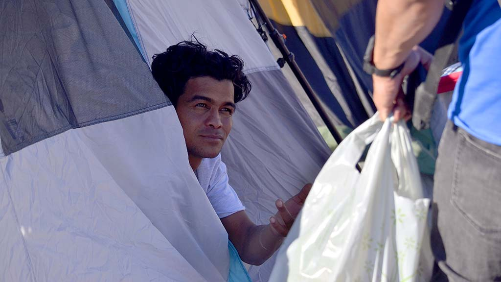 A migrant reaches out of his tent to receive a first-aid kit.